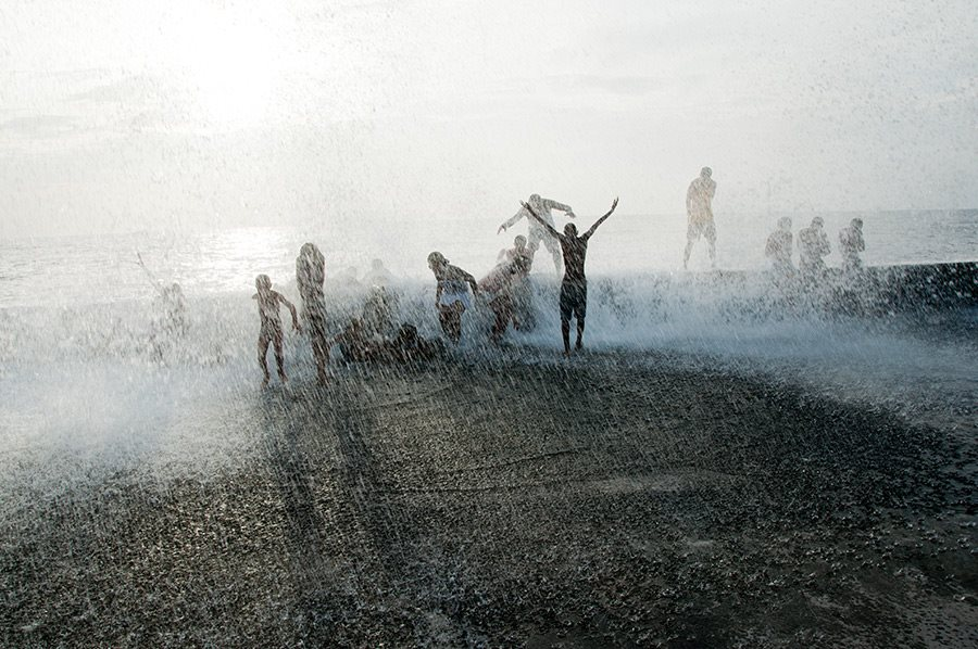 people playing with water in malecon of havana in my photo tours in cuba