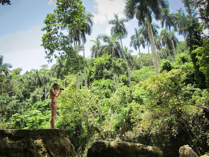 photos of tourism in Cuba woman into the jungle taking a photography