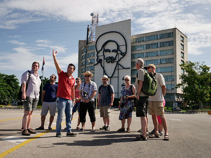 camilo cienfuegos in revolution square with his beard and many tourist in tours around cuba
